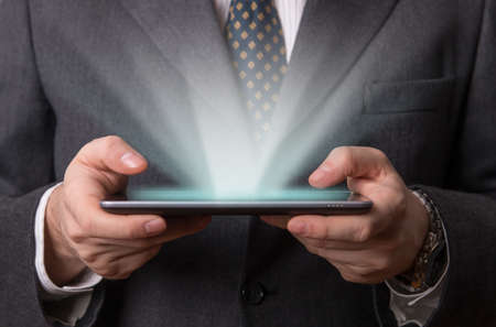 holographic: Businessman working on his holographic futuristic tablet
