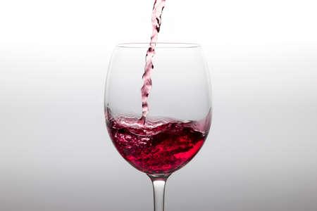 Red wine poured into a glass on a white backgorund Zdjęcie Seryjne
