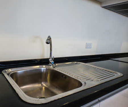 worktop: bowl stainless steel kitchen sink on a black granite worktop Stock Photo