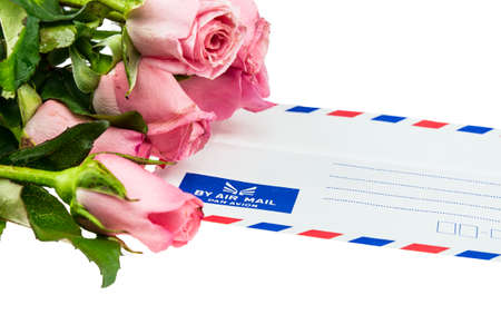 Pile of pink rose blossoms with White Vintage Envelope on white background photo