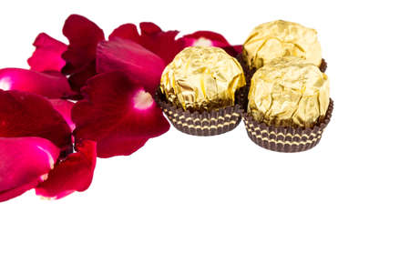 scattered in heart shaped: Red rose petals  with Chocolate ball on white
