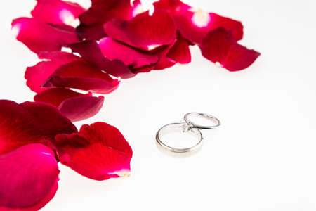 scattered in heart shaped: Red rose petals  with diamond ring on white