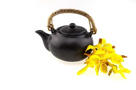 yellow tea pot: Black tea pot with Mokkara yellow Orchid flower isolated on white Stock Photo