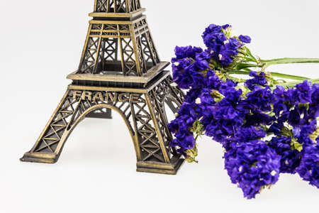 eiffel tower model and Statice flower isolated on white photo