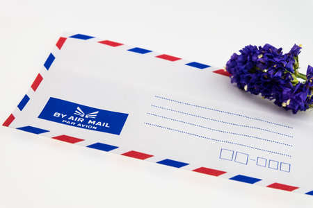 Air mail envelope and Statice flower isolated on white photo