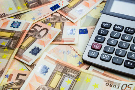 stack of 50 Euro money and calculator Standard-Bild