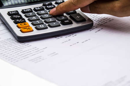 bank statement and calculator with finger pressing Standard-Bild