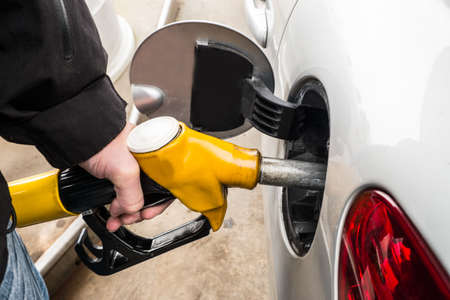 fueling pump: Hand refilling the car with fuel