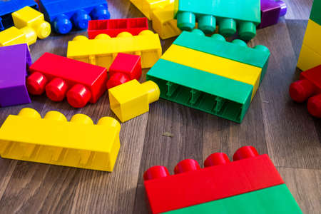yellow lego block: Small pile of colorful childrens building bricks on wood. Stock Photo