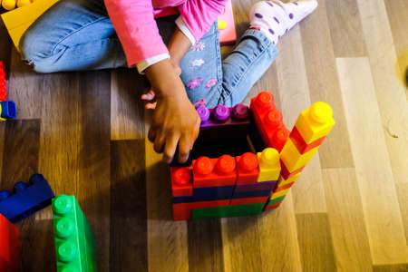yellow lego block: gril playing building brick toy.