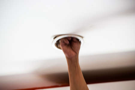 downlight: Hand fixing downlight. Stock Photo