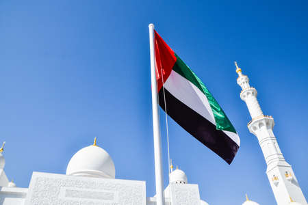 ABU DHABI, UAE - November 7, 2015: A United Arab Emirates flag flying  with Sheikh Zayed Mosque in Abu Dhabi as background.