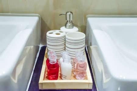 Bath accessories on black shelf near white wash basin.