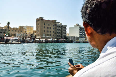 shipbuilding: Dubai, United Arab Emirates -November 6, 2015: man on traditional abra ferries on November 6,2015 in Dubai, UAE. Shipbuilding technology is unchanged from the 18th century. Editorial