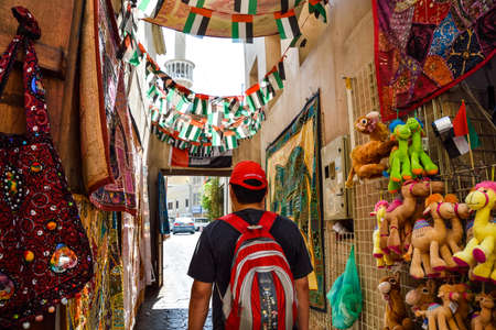 Dubai, United Arab Emirates -November 6, 2015: backpack man with red hat among Shops  in  souq Bur Dubai in the old city centre Editöryel