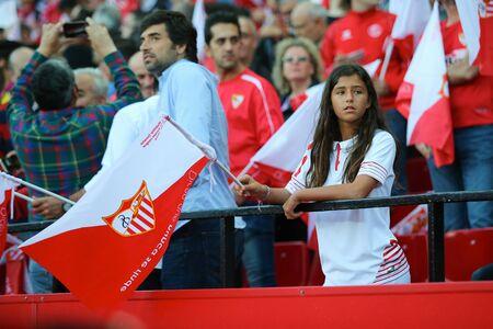 sevilla: SEVILLA, SPAIN - MAY 5: Sevilla FC girl-fan stays on the stands with a flag during the UEFA Europa League second leg semi-finals match between FC Shakhtar Donetsk vs Sevilla FC, 5 May 2016, Ramon Sanchez Pizjuan, Spain