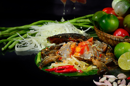 Thai salad material (SomTum) blue swimming crab fresh (Portunus pelagicus)on banana leaf on black background & raw material  popular thai Food.