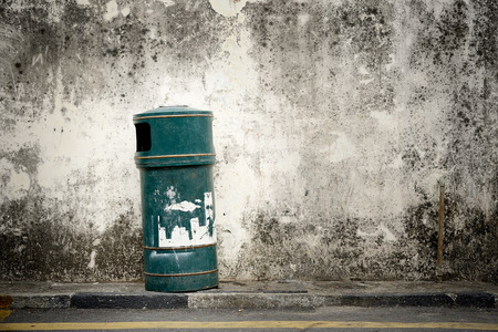 green bin with street wall background