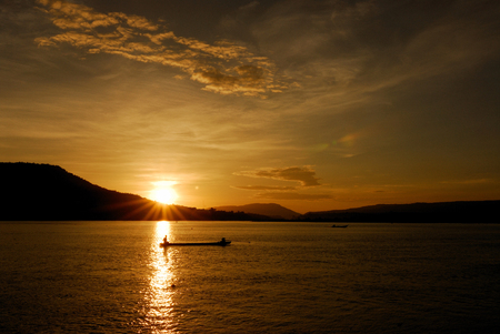 Men fishing on the Mekong River in a field at sunset, Chiang Khan, Thailand photo