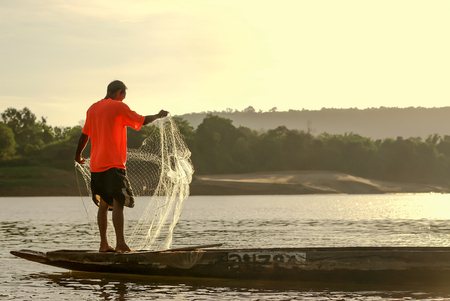 mekong river: Men fishing on the Mekong River in a field at sunset Chiang Khan Thailand Stock Photo