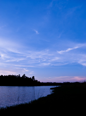 gloaming: Beautiful sky landscape with sunset over river bank Stock Photo
