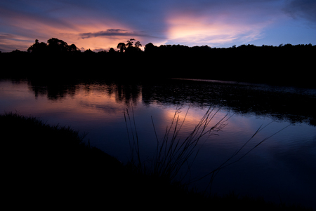Beautiful sky landscape with sunset over river bank Stock Photo