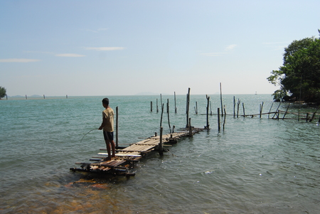 pontoon: The boy stand on pontoon and  fishing in the sea