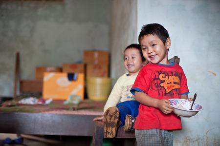 Pakse, Laos, il 14 agosto: Un non identificato Laos bambino seduto a mangiare in casa di Pakse, Laos il 14 agosto 2010