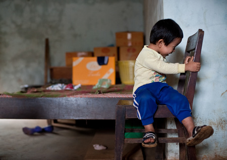 laotian: PAKSE, LAOS, August 14 : An unidentified Laos little boy sitting eating in the house of PAKSE, LAOS on August 14, 2010