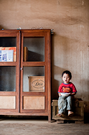 unicef: PAKSE, LAOS, August 14 : An unidentified Laos little boy sitting eating in the house of PAKSE, LAOS on August 14, 2010