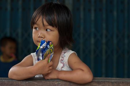 CHIANG MAI TAILANDIA - 23 OTTOBRE: i bambini non identificati mangiano gli spuntini nel loro villaggio il 23 ottobre 2009 in CHIANG MAI, TAILANDIA