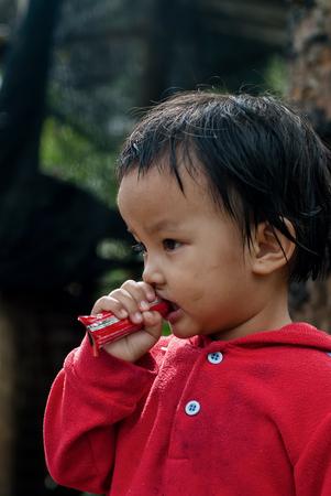 CHIANG MAI THAILANDIA - 23 ottobre: ??i bambini non identificati mangiare spuntini nel loro villaggio il 23 ottobre 2009 a Chiang Mai, Thailandia