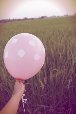Hand hold blank pink balloon mock up isolated. Baloon mockup art design. Pattern, logo, natural background