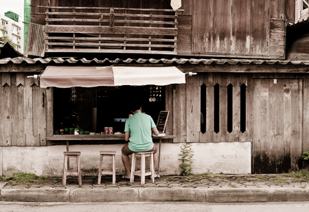 LAMPANG THAILAND - AUGUST 2 : unidentified man at Street cafe coffee in old town village on August 2, 2015 in LAMPANG, THAILAND