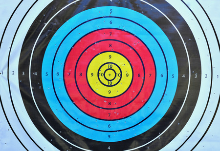 Archery target close up with many arrow holes in gold red blue and black