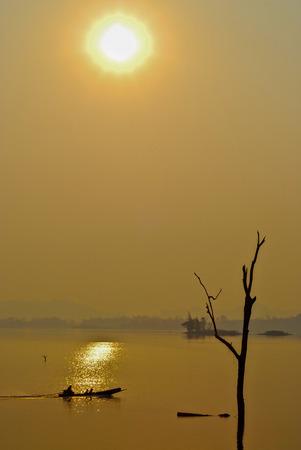 mirror: Beautiful view shadows Light Long-tailed boat sunrise in dam Srinakarin National park Kanchanaburi, Thailand Stock Photo