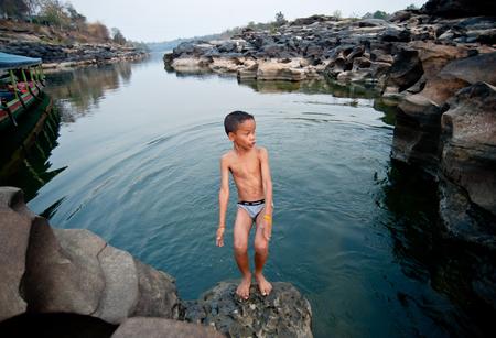 SAMPANBOK UBONRATCHATHANI - FEBRUARY 26 : Activities on the mekong river, children swimming and playing rock holes Stone View Sam Pan Bok (Grand Canyon) FEBRUARY 26, 2011 in UBON RATCHATHANI, THAILAND