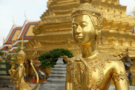 Golden Kinnari statue at Temple of Emerald Buddha (Wat Phra Kaew) in Grand Royal Palace. Half-bird, half-woman, Bangkok, Thailand