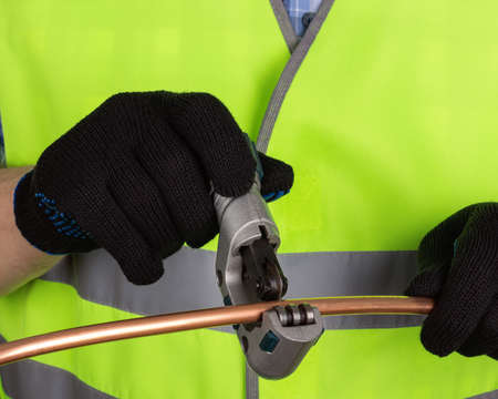 copper pipe: Master in black gloves cutting a copper pipe with a pipe cutter. Isolated on white background Stock Photo
