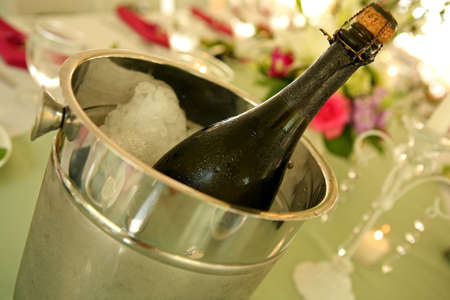 champagne in een ijsemmer op een tafel op een bruiloft Stockfoto