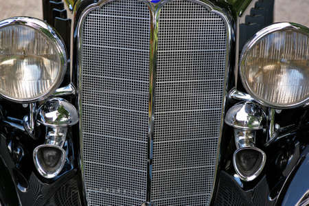 close up of a vintage black cars grill and headlamps