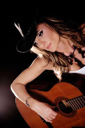 Beautiful Woman in Country Westren Fashion Playing A Guitar photo