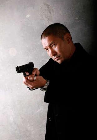Asian Man Pointing a Gun