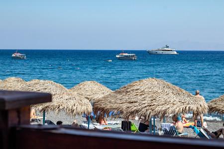 Tiki huts on Black Beach, Santorini Greece