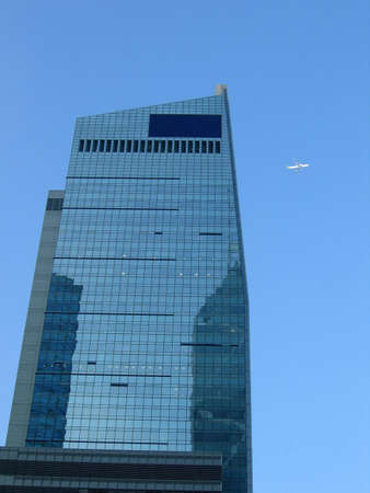 financal: Corporate building with a plane on the blue sky, place st the top of the building for text input