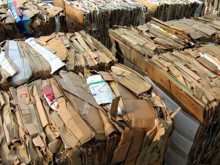 pile reuse: Cubes of packed corrugated paper and newspaper ready to recycle Stock Photo