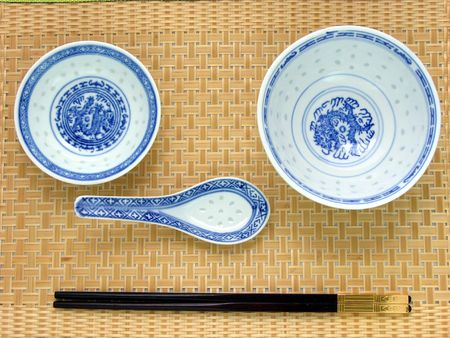 Traditional chinese table setting: Chinese bowl, spoon, plate, cropsticks on bamboo mat