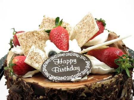 chocolate birthday cake: Toppings of a chocolate birthday cake in isolated white Stock Photo