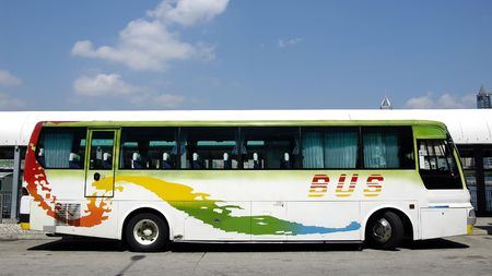 Tour bus in white with red, yellow, green and blue pattern