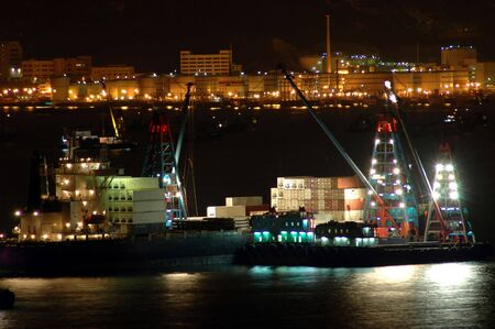 Cargo ships in the habour work at night Stock Photo